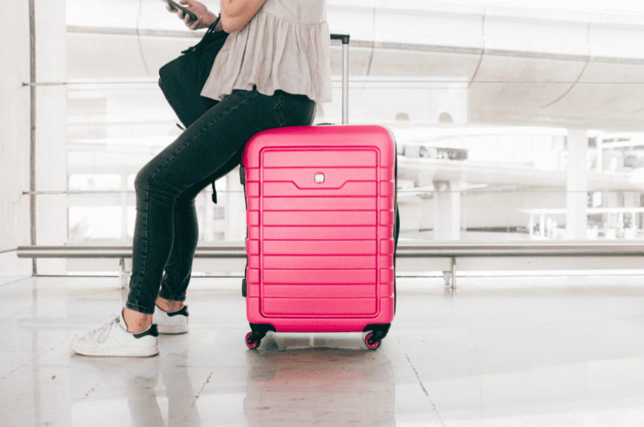 A woman leaning against a neon pink suitcase.