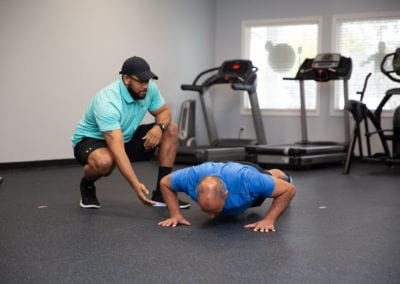 A personal trainer guiding proper form on pushups